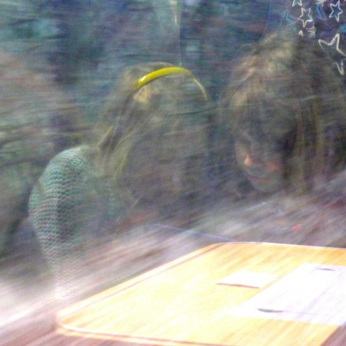 Zwei Freundinnen stecken während der Zugfahrt die Köpfe zusammen
